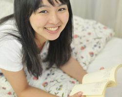 ベッドに寝転んで読書をしている女性